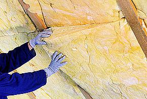 Handwerker*in dämmt das Dach mit einer Zwischensparrendämmung.