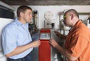 Zwei Männer stehen neben einer Wärmepumpe im Heizungskeller