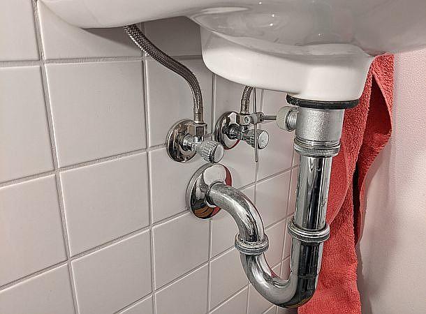 Blick unters Waschbecken: Ventil für Warmwasser, Kaltwasser, Abflussrohr, im Hintergrund ein rotes Handtuch
