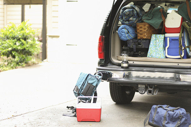 Auf dem Bild ist ein Auto mit viel Gepäck im und am Kofferraum zu sehen.