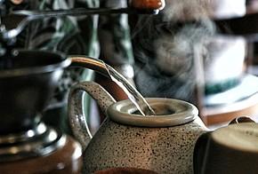 Graue Teekanne wird mit Wasser aufgegossen, vorne Links ist angeschnitten eine Kaffeemühle zu sehen.