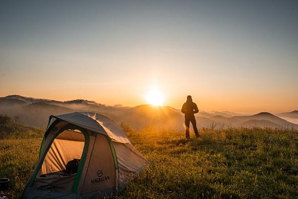 Auf dem Bild ist ein Mann mit einem Zelt in der Natur zu sehen.
