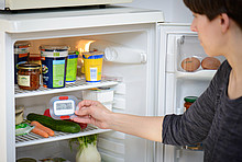 Frau nimmt Thermometer aus Kühlschrank