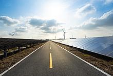 Windräder und Solaranlagen an einer Straße.