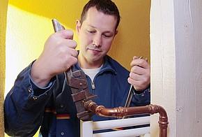 Handwerker-Botschafter Christian Klemm tauscht für den hydraulischen Abgleich ein Ventil aus.