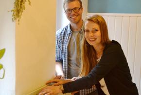 Eine junge Frau und ein junger Mann stehend lächelnd neben einer Heizung. Sie wollen das Thermostat der Heizung tauschen.