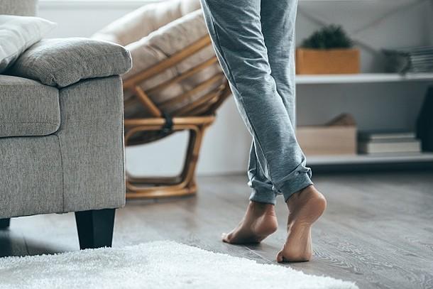 Eine Frau geht barfüßig über den beheizten Fußboden.