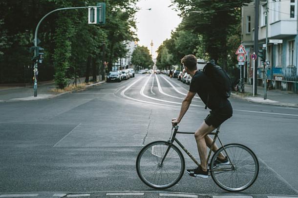 Auf dem Bild ist ein Fahrradfahrer in der Stadt zu sehen.