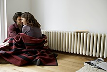 Ein Paar in Decke vor der Heizung