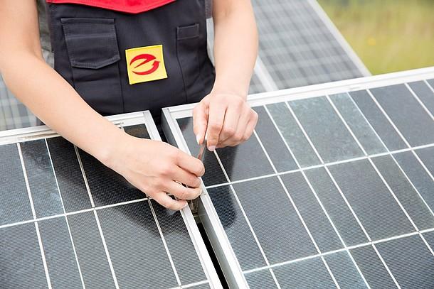 Handwerksperson bei der Montage einer Photovoltaik-Anlage.