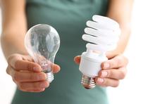 Frau zeigt zwei Glühlampen
