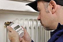 Handwerker stellt das Thermostat ein.