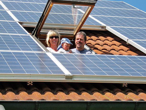 Solarmodule auf einem Dach mit Dachfenster, aus dem Frau, Baby und Mann herausschauen