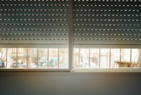 Fenster mit halb geöffneten Rolladen