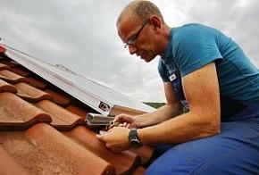 Handwerker schließt einen Kollektor für eine Solarthermieanlage auf dem Dach an.