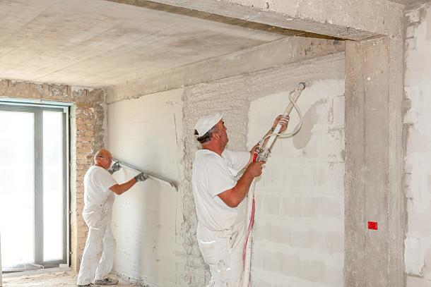 Zwei Männer bringen Dämmputz an die Wand.