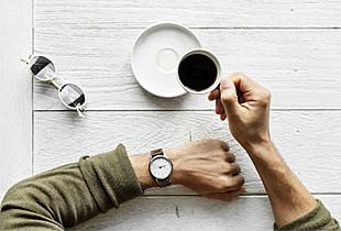 Mann trinkt Kaffee und schaut auf Armbanduhr