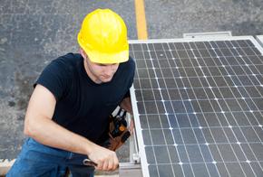 Monteur an einem Solarmodel einer Photovoltaikanlage