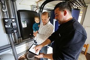 Hausbesitzer mit Baby und Handwerker vor der Heizanlage im Keller