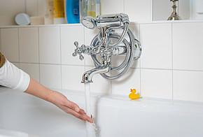 Auf dem Bild sind eine Badewanne, laufendes Wasser und eine ein Arm zu sehen.