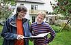Energieberater mit Unterlagen und Hauseigentümer im Garten, im Hintergrund ein zweigeschossiges Haus