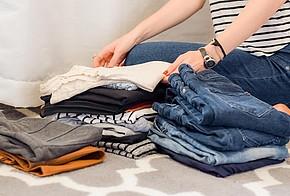 Eine Person sortiert Kleidung auf 3 verschiedene Stapel.
