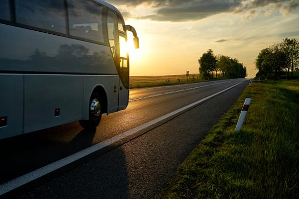 Auf dem Bild ist ein Reisebus auf einer Straße zu sehen.