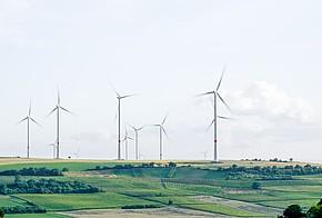 Windräder auf einer grünen Landschaft. Das Erneuerbare-Energien-Gesetz (EEG) soll den Ausbau von erneuerbaren Energien und Ökostrom fördern