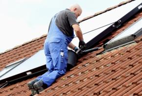 Handwerker schraubt Solarleitung ab.