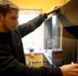 Handwerker montiert Abdeckung der Heizanlage.