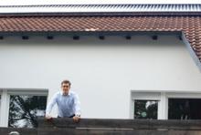 Christoph Kniehase auf seinem Balkob. Darüber befinden sich die Solarthermiekollektoren.