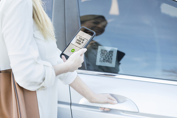 Eine Frau öffnet ein Carsharing-Auto per App.