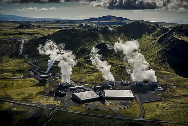 Hellisheidi Power Plant in Island: Luftaufnahme der Industrieanlage mit viel Wasserdampf, umgeben von Grün und Bergen.