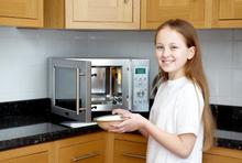 Mädchen erwärmt Essen in Mikrowelle