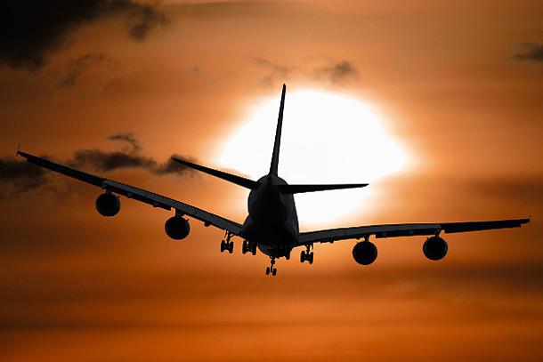 Ein Flugzeug fliegt in den Sonnenuntergang.