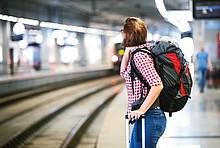 Frau wartet im Bahnhof auf einen Zug.