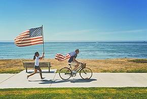 Fahrradfahrer und Joggerin mit USA-Flaggen
