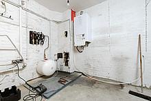 Auf dem Bild ist ein Keller mit einem Heizkessel zu sehen.