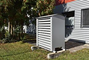Luftwärmepumpe mit Einhausung vor einem Haus