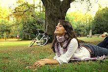 Eine Frau genießt die frische Luft im Park.