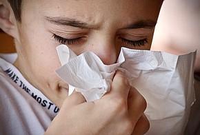 Allergiker niest in ein Taschentuch