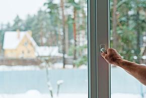 Mann öffnet Fenster