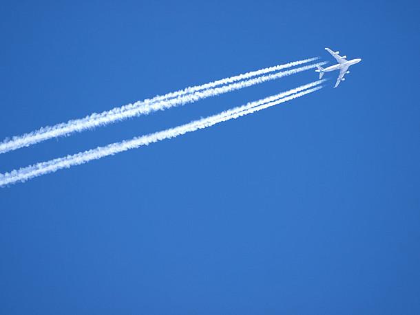 Flugzeug in großer Höhe mit Kondensstreifen