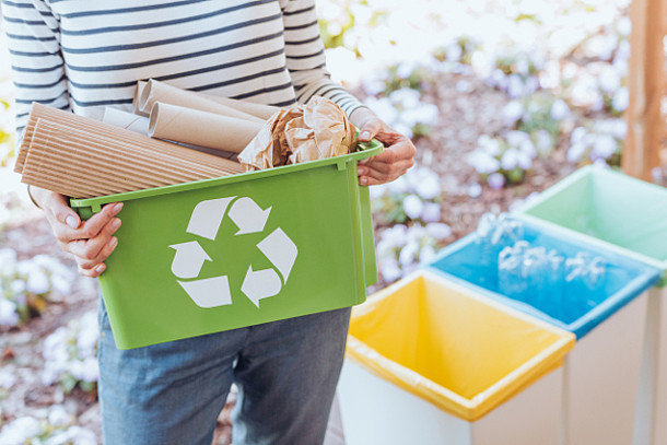 Frau hält einen Recycling-Behälter mit Papier.