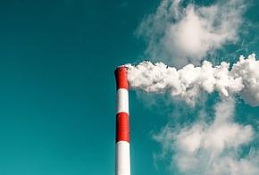 rot-weiß gestreifter Schornstein vor blauem Himmel. Weißer Rauch steigt aus Schornstein auf.