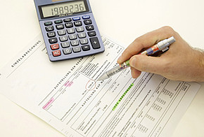 Heizkostenabrechnung mit Taschenrechner und Stift haltender Hand