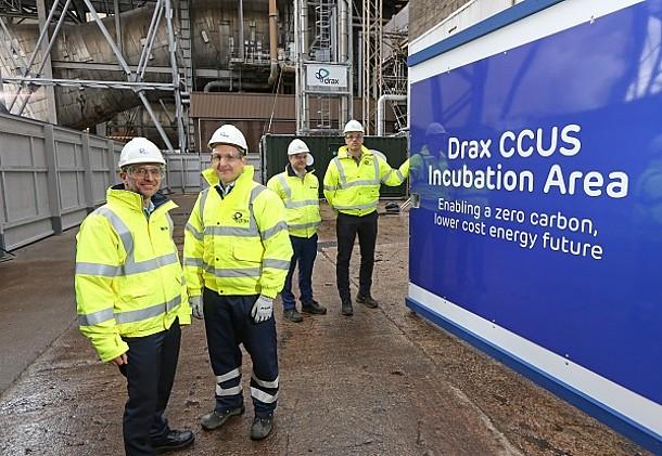 Vier Verantwortliche mit neongelben Jacken und weißen Schutzhelmen an der Drax-BECCS-Anlage in England.