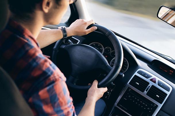 Auf dem Bild ist ein Mann im Auto zu sehen.
