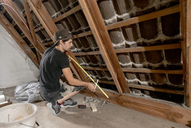 Auf dem Foto ist ein Handwerker beim Dachdämmen abgebildet.