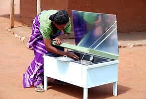 Frau mit Solarkocher vor einer Lehmhütte